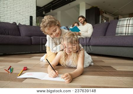 Happy Siblings Playing Peek A Boo Or Guess Who Drawing On Warm Wooden Floor While Parents Reading Bo