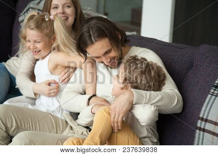 Happy Parents And Children Laughing Having Fun Tickling On Sofa, Cheerful Mom And Dad Embracing Kids