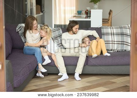 Cheerful Parents Playing With Kids On Sofa Laughing Together At Home, Mom And Dad Having Fun Ticklin