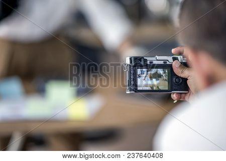 Man Holding Vitage Camera And Taking Photos At Studio