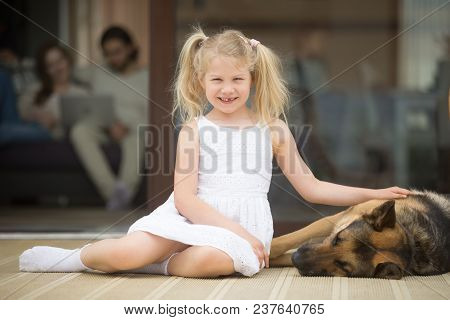 Smiling Girl Playing With Dog Outside Country House Looking At Camera, Little Kid Stroking Caressing