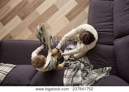Father And Son Enjoy Pillow Fight On Sofa, Happy Dad And Little Boy Having Fun Together At Home In L