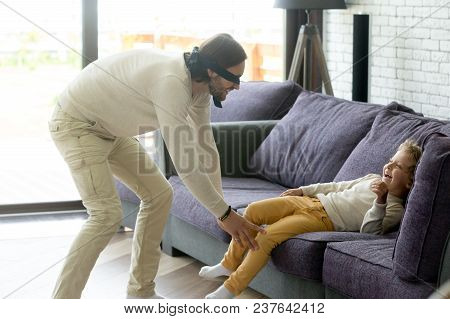 Dad And Son Playing Hide And Seek Game At Home, Blindfolded Father Trying To Catch Excited Happy Chi