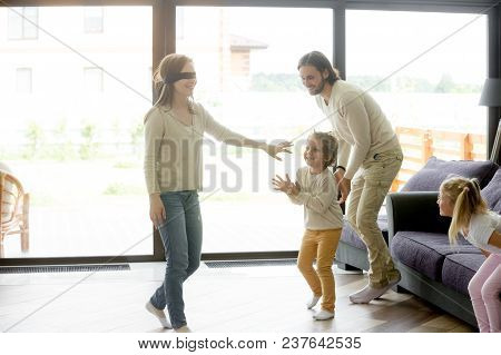 Excited Kids Playing Hide And Seek Active Game With Blindfolded Mom, Happy Family Having Fun Togethe