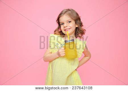 Pretty Girl In Yellow Dress Holding Glass With Drink And Straw Smiling At Camera On Pink.