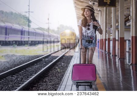 Young Beautiful Woman With Pink Luggage Walking On Platform Of Railway Station Waiting For Train Arr