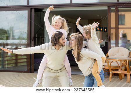 Happy Parents Piggybacking Son And Daughter Outdoor, Smiling Mom And Dad Holding Cute Kids On Back S