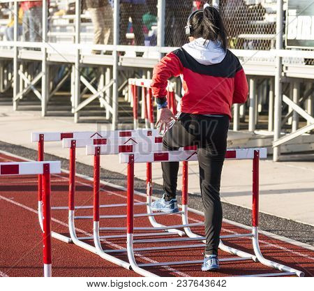 A Female Hurdle Runner Is Doing Walk Over Hurdle Drills Preparing For Her Race While Wearing Headpho