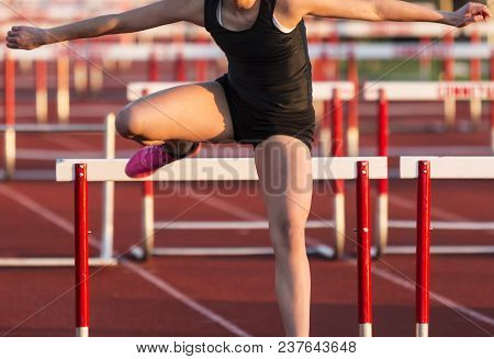 A High School Female Is Sprinting Over Hurdles And Landing Close To The Hurdle During A Race.