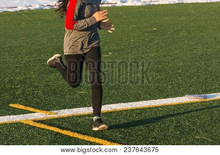 A High School Female Runner Is Running Fast On A Green Turf Field Iin The Winter, With Snow Lining T