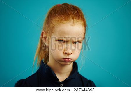 Red-haired Girl With An Offended Face And Inflated Mouth Looks Into The Camera, Furrowed Her Eyebrow