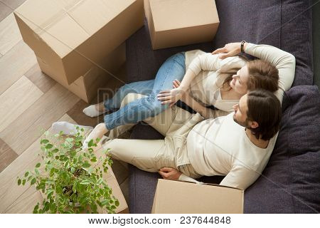 Relaxed Couple Resting On Sofa On Moving Day, Young Renters Relaxing On Couch Moved Into Apartment W