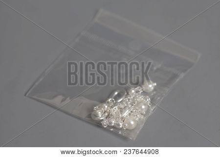 Silver Jewelry In A Plastic Bag On Gray Background