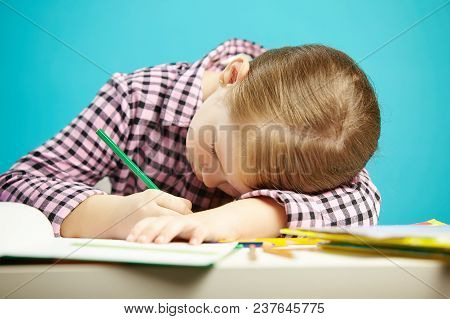 Isolated Shot Of Child With Poor Posture Sitting At Desk And Do Homework. Girl Rested Her Head On Ta