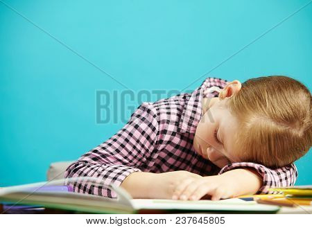 Tired Girl Fell Asleep At Desk While Solving A Problem Or Reading. Schoolgirl Sleeping Around The Ta