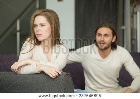 Unhappy Young Couple Arguing, Offended Affronted Woman Ignoring Angry Man Sitting Her Back To Jealou