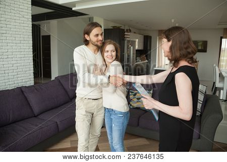 Smiling Young Couple Handshaking Real Estate Agent Buying Or Renting New Home, Satisfied Customers R