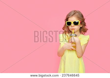 Pretty Little Girl In Dress And Sunglasses Posing On Pink With Glass Jar Of Cocktail Chilling.