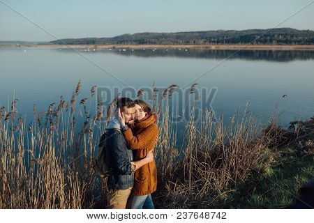 Young Loving Couple On The Lake Near The Reeds