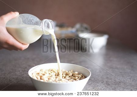 Teenage Girl Hands Pour Milk From Plastic Bottle In White Bowl With Puffed Wheat Flakes On Grey Grun