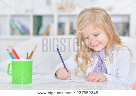 Portrait Of Cute Little Girl Drawing With Pencils