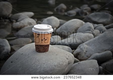 Brown Paper Coffee Cup With White Plastic Lid Lies On The Stones
