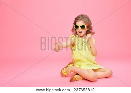 Wonderful Happy Girl In Yellow Dress And Sunglasses Holding Thumb Up Sitting On Pink Backdrop.