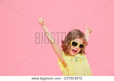 Excited Expressive Wonderful Happy Girl In Yellow Dress And Sunglasses Holding Hands Up In Great Hap