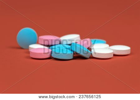 Multicolor Vitamins Drugs Pink, Blue And White On Orange-brown Background