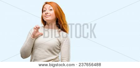 Beautiful young redhead woman proud, excited and arrogant, pointing with victory face isolated over blue background