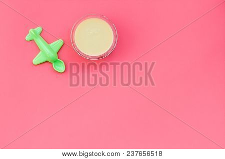 Healthy Food For Little Baby. Puree With Near Toys On Pink Background Top View.