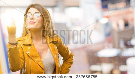 Beautiful young woman angry gesturing typical italian gesture with hand, looking to camera at restaurant