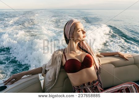 An Attractive Young Girl With A Headscarf On Her Head Relaxes On Her White Yacht, Enjoys Sea Voyage