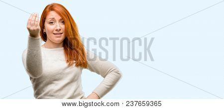 Beautiful young redhead woman angry gesturing typical italian gesture with hand, looking to camera isolated over blue background