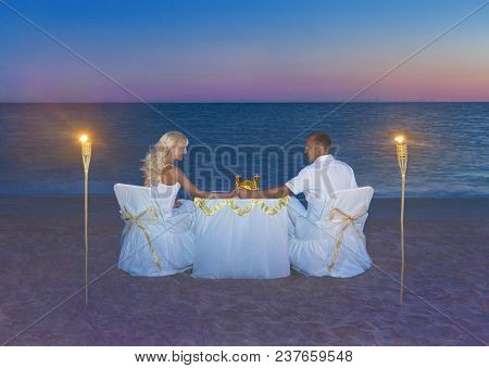 Loving Couple In White Cloth At Romantic Dinner With Torch Flares, Candles And Luxury Decorated Tabl