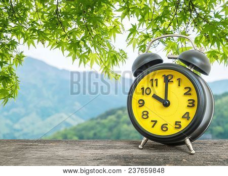 Closeup Black And Yellow Alarm Clock In Ten O'clock On Leaves And Mountain View Textured Background