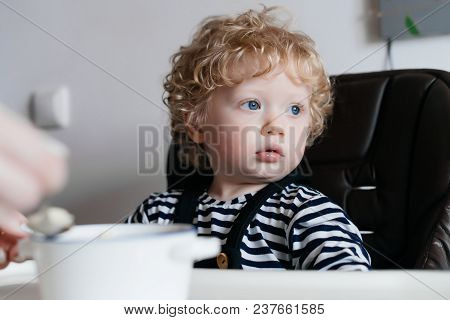 Curly Little Baby Boy Sitting In A Highchair In The Kitchen, Mum Is Feeding A Useful Porridge