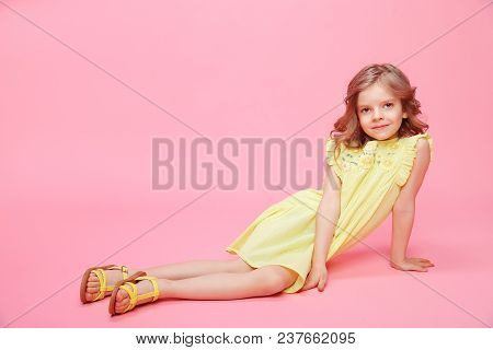 Little Adorable Model In Summer Yellow Dress And Sandals Posing On Pink Backdrop In Studio.