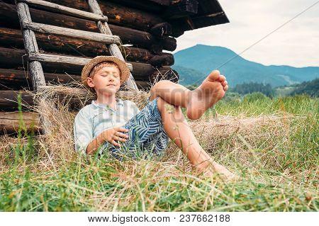 Boy In Straw Hat Lies In Hay Near The Barn
