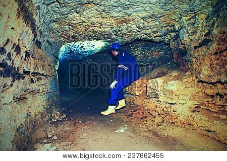 Hunched Worker In A Blue Overall And A Safety Helmet Work In Underground Tunnel. Dangerous Employmen