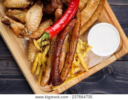 Mixed Fresh Grilled Meat And Sausage With Pepper, French Fries And Sauce On Wooden Cutting Board. As