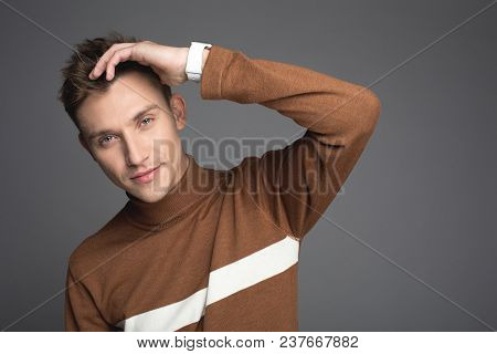 Portrait Of Good Looking Guy Touching His Soft Hair. He Is Looking At Camera With Calmness. Isolated
