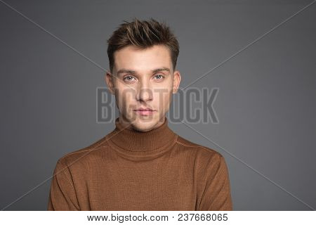 Portrait Of Gorgeous Man Staring At Camera. His Expression Is Serious. Isolated On Background