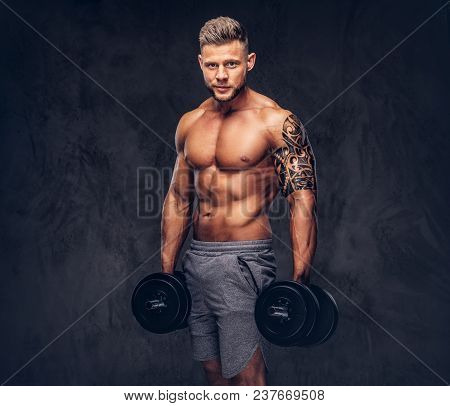 Powerful Stylish Bodybuilder With Tattoo On His Arm, Posing With Dumbbells In A Studio. Isolated On