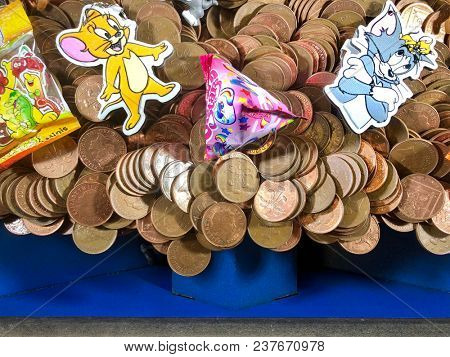 SOUTHWOLD - APRIL 24, 2018: Two pence coins sitting precariously at the edge of the winnings chute at an amusement arcade in Southwold, Suffolk, UK.