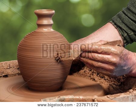 Potter Makes A Clay Vase On A Pottery Wheel. Potter Makes A Pattern With A Fork.