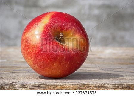 Red Juicy Solid Apple Under Sunlight On A Blackboard Against A Gray Wall