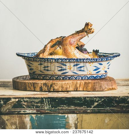 Roasted Whole Chicken For Christmas Eve Celebration Table On Rustic Wooden Board, Light Grey Wall Ba