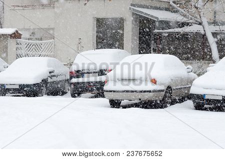 Back Side Of Parked Cars Covered With Snow While Snowing, White Building In Background