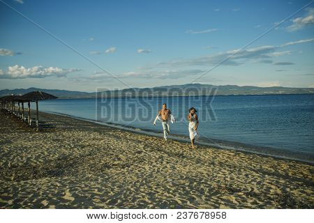 Man And Woman Walking, Couple Happy On Vacation. Couple In Love Running On Beach, Seashore. Couple I